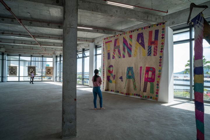 An industrial gallery space with large windows running along its lengths features an immense mat that hangs from floor to ceiling and features a small dolphin along with the words 'Tanah & Air'.