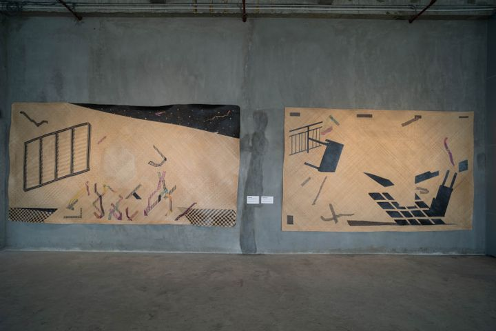 Two black and beige mats are shown on a grey concrete wall. In black, tables are featured, some of them fragmented so that the pieces are distributed across the picture planes.