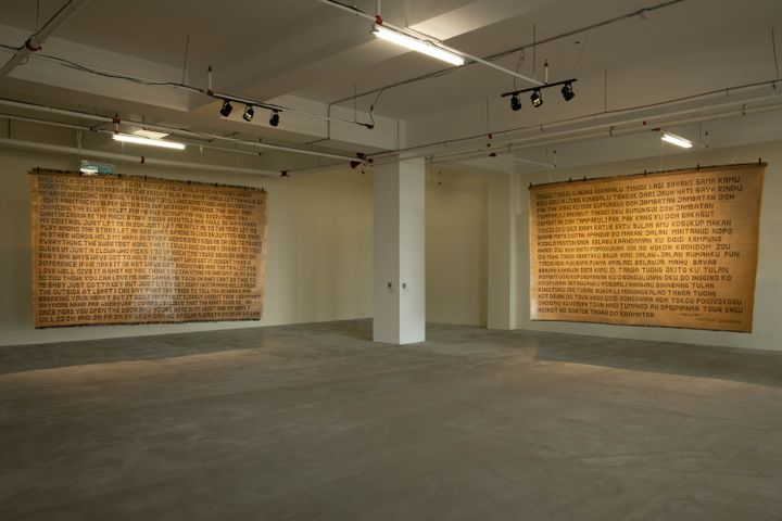 Two large mats, beige in colour, feature illegible writing across their surfaces. They are hung in a dimly lit gallery room.