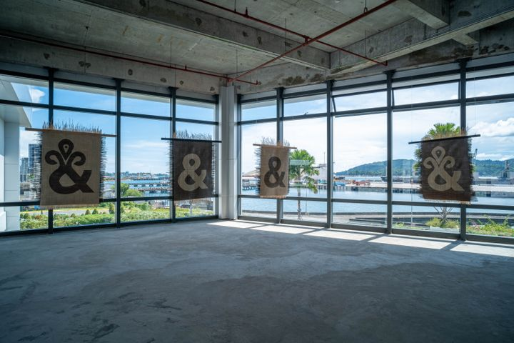 Four mats hang from the ceiling against windows looking out to sea. Each mat, created by Yee I-Lann and her collaborators, features the '&' sign, with shapes that have been reinterpreted.