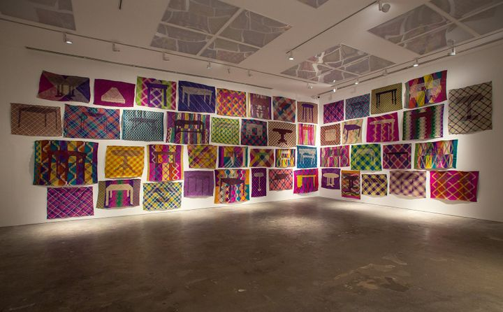 Colourful patterned mats are hung along two adjoining walls in a cluster at Silverlens' dimly lit gallery.