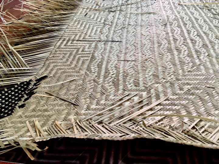 A mat in the process of being woven is photographed on the floor close up, so that the unfinished, frayed ends of the threads are visible, as is a died black patterned segment.