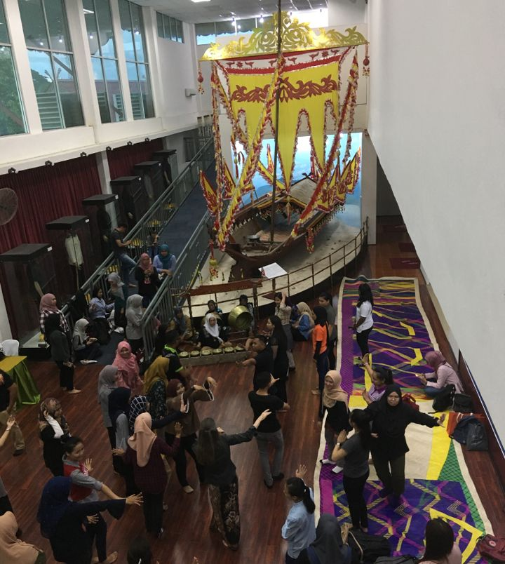 For the launch of the artist's exhibition, academics, Sabah Museum staff and Universiti Malaysia Sabah students dance, sit and get comfortable on the Tikar-A-Gagah as an all woman Kulintangan orchestra plays in the foyer in front of the museum's Lepa houseboat with an impressive Sambulayang sail/flag.