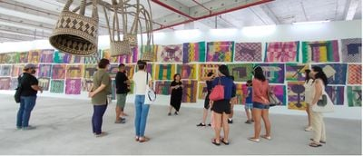 12 individuals stand in the gallery space as artist Yee I-Lann leads an exhibition tour of her Borneo Heart exhibition. A series of colourful mats featuring imagery of tables runs the length of the room.