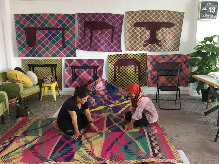 Artist Yee I-Lann and one of her collaborators are inspecting a colourful patterned mat that has been laid out on the floor in a hip, furnished room.