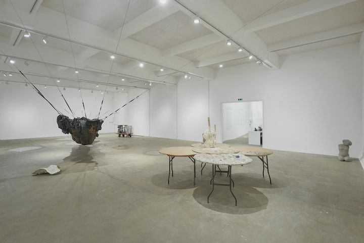 An installation by Yu Ji in the gallery space, featuring a set of three round tables with sculptures placed on top, and a black hammock-like structure made of netting and tarpaulin stretching from one side of the gallery to the other.