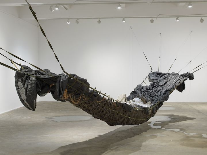 An installation by Yu Ji in the gallery space, featuring a large hammock made of netting and black tarpaulin in the gallery space, with a pool of water beneath it.