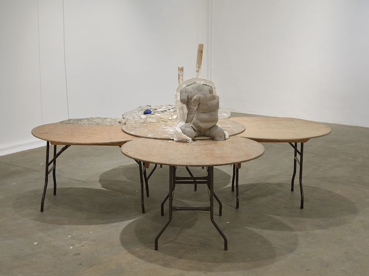 An installation in the gallery space by Yu Ji, featuring five overlapping round tables. In the centre, a cement torso sits upright.