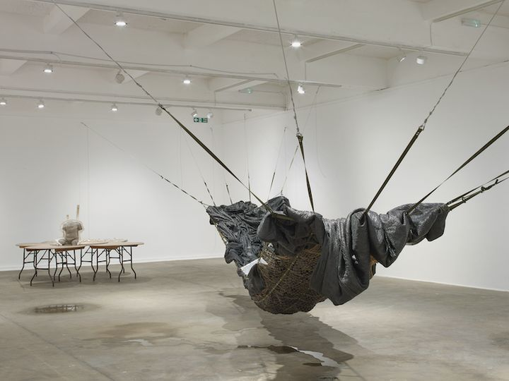 An installation by Yu Ji in the gallery space features a large black hammock-like structure hanging from wall to wall, and a set of five circular overlapping tables support a torso made from cement at their centre. The table are to the left, and the hammock is to the right.