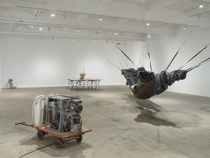 An installation by Yu Ji in the gallery space features three distinct works: a large hammock-like structure to the left, which hangs from wall to wall, a set of five circular overlapping tables with a torso made from cement at their centre, to the far left, and at the front, there is a machine made up of two milk canisters that sit atop a trolley.
