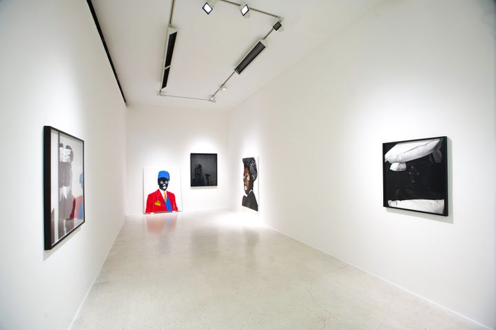 In a white gallery space, framed black and white photographs by Zanele Muholi sit along the walls. At the far end of the gallery, a bright red portrait sits against the wall on the floor.