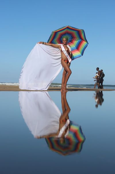 Zanele Muholi's artwork depicting a female Mambo dancing on the beach holding a rainbow umbrella, flapping her white cape