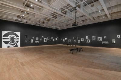 Exhibition at Tate Modern of Zanele Muholi's artworks across the gallery walls which are painted black