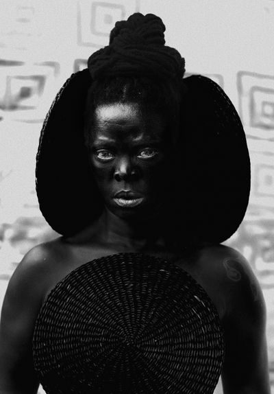 A highly contrasted photograph of Zanele Muholi features the artist with black disks adorning their head, as they gaze out at the viewer assertively.