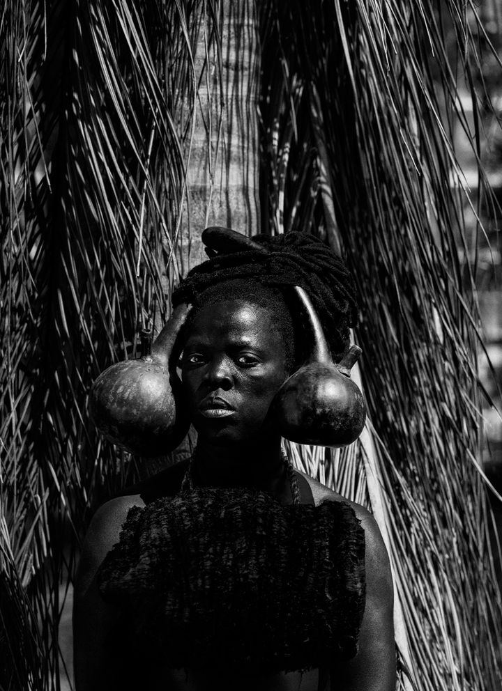 A portrait of artist Zanele Muholi captures the artist with two gourds resting either side of their head. Their gaze fixes the viewer.