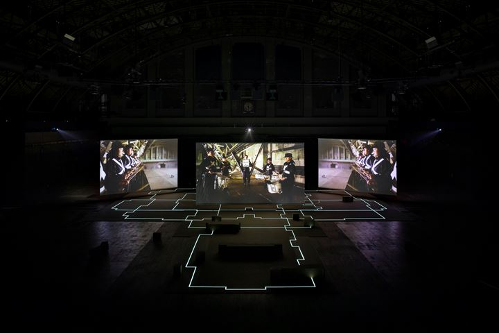 Hito Steyerl, Drill (2019). Video installation, environment; three-channel HD video, colour, sound. 21 min. Environment: EL tape, MDF seating. Exhibition view: Drill, Park Avenue Armory, New York (21 June–20 July 2019). Courtesy the artist, Andrew Kreps Gallery, New York; Esther Schipper, Berlin. Photo: © James Ewing.
