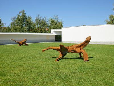 Two corten steel tree fragments sit on a neat lawn.