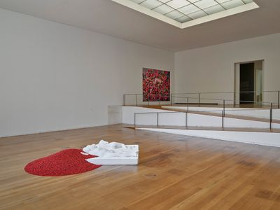 In the centre of the exhibition space, a plaster cast sculpture features Ai Weiwei lying on a mattress naked beside a woman. Black and red beads spill from his head.