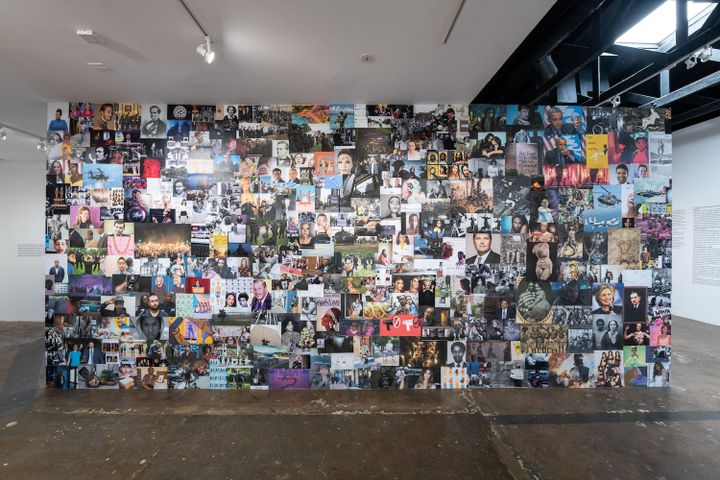 A series of pop cultural and historical images pertaining to racial politics are collaged on a wall that is erected in the gallery space.