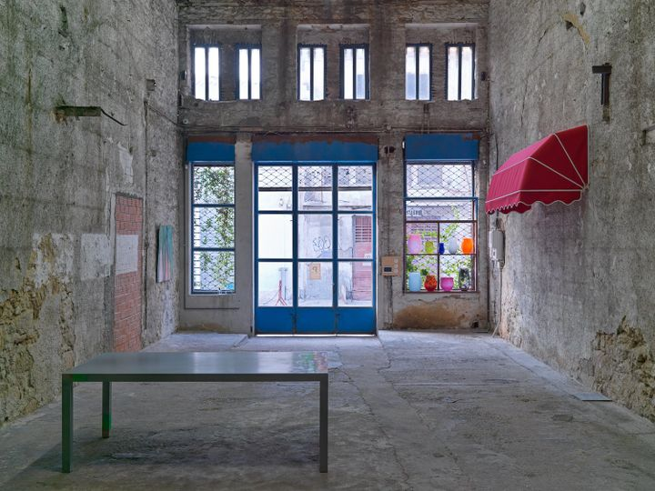 A sparse but well lit gallery space shows an exhibition of works by Christodoulos Panayiotou, including red awning attached to the wall to the right and a table in the foreground.