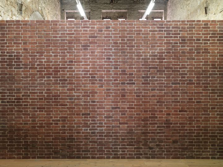 A fake brick wall separates the gallery space of Rodeo in Athens.