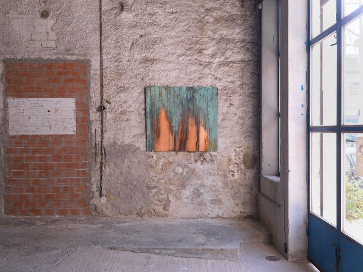A blue-tinted sheet of copper hangs on a brick wall in Rodeo's Athens gallery.