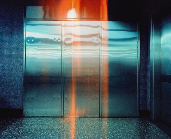 A metallic door in Causeway Bay station in Hong Kong features a glitch of yellow light spilling down its centre.