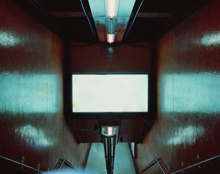 A photograph by Christopher Button features a clean, red stairwell of Central divided by a handrail, an over-exposed, white advertising screen bathing the scene in a cinematic, electric blue.
