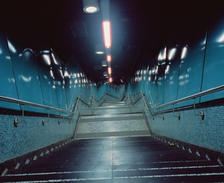 A photographer by Christopher Button pans down flight of aqua terrazzo stairs in Quarry Bay station in Hong Kong, lined with black rubber safety edges on each step that match the blackened ceiling.