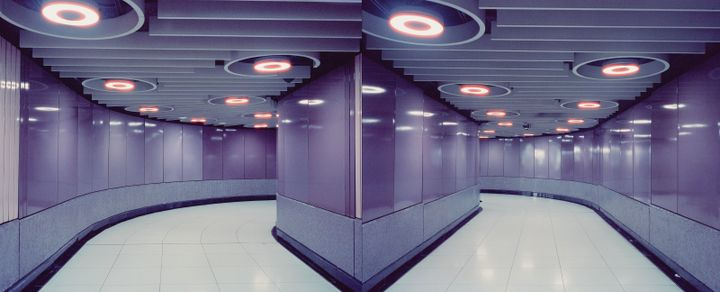 A diptych by Christopher Button features two photographs of a corridor in Causeway Bay station in Hong Kong, the walls gleaming shiny purple and lit up by rings of light on the ceiling.