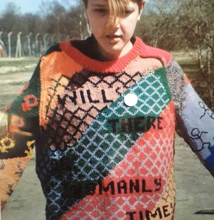 An archival colour photograph of a Greenham Common protester in a sweater that reads 'Will There Be Womanly Times?'