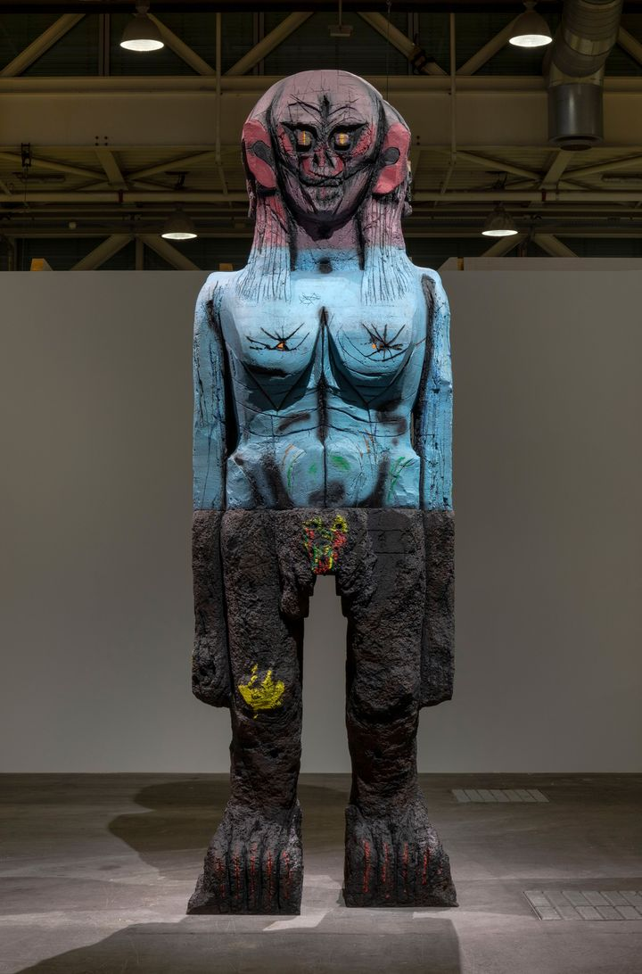 A totemic sculpture by Huma Bhabha that features a many-faced head  painted red, a blue torso, and black legs.