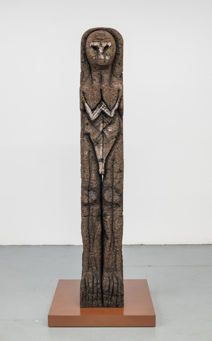 A totemic sculpture by Huma Bhabha in shades of brown that resembles a mix between a neolithic sculpture and an owl.