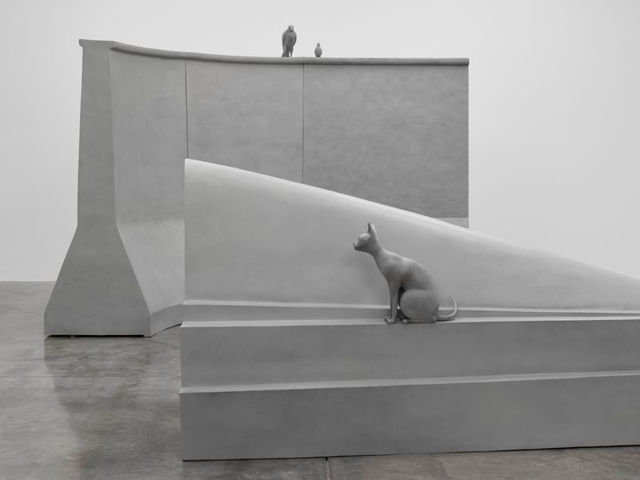 Artist Liu Wei's exhibition depicting 2 concrete-hued large-scale blocks with a cat sat on top and 2 birds perched on the higher block