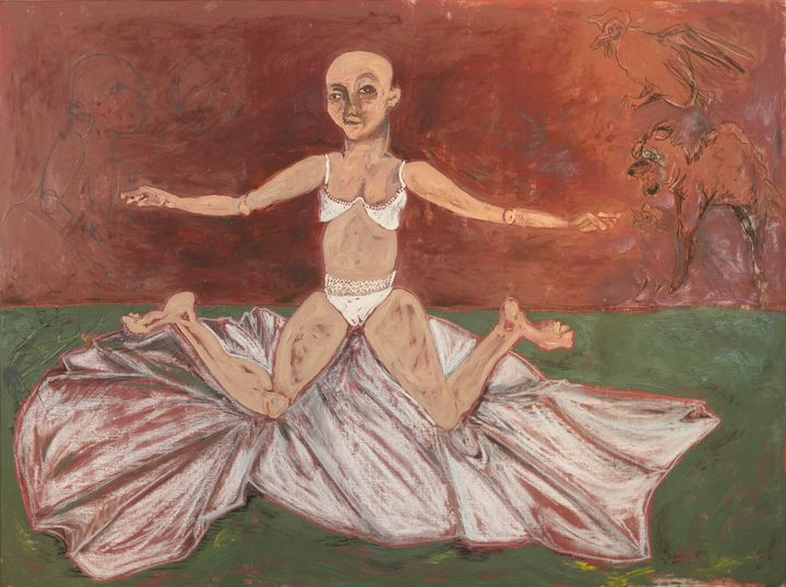 A figure sits on a cloth on a floor with their legs splayed.