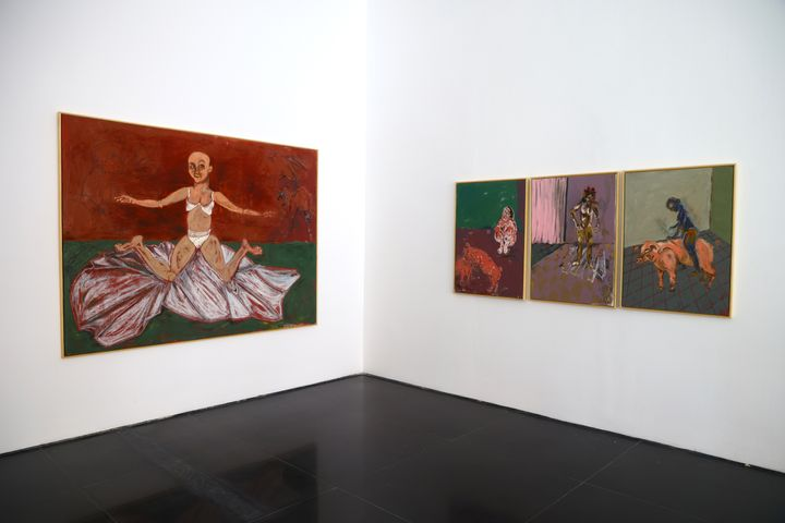 Two white walls in the gallery space feature on the one side, a large canvas encompassing a figure sitting on the floor with their legs splayed against a red background, and three paintings in a line to the right featuring pigs, roosters, and figures engaged in ambiguous activities.