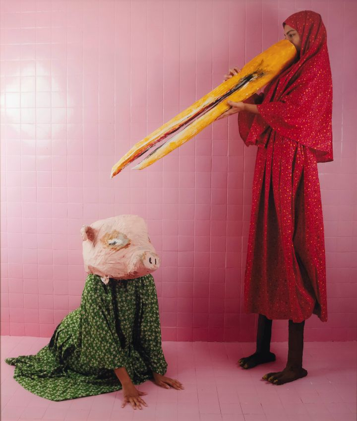 Two figures are staged in a pink-tiled room, one sitting on the floor to the left with a papier-mâché pig head, and the other to the right holding a long bird's beak to their face and with feet under her red dress that resemble those of a bird.