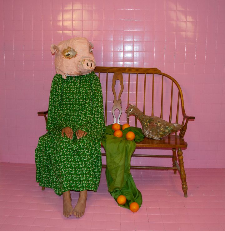 A figure in a green dress sitting on a bench in a pink-tiled room sits with a papier-mache pig head. There are oranges placed on the bench next to her, and she sits with her hands on her knees.