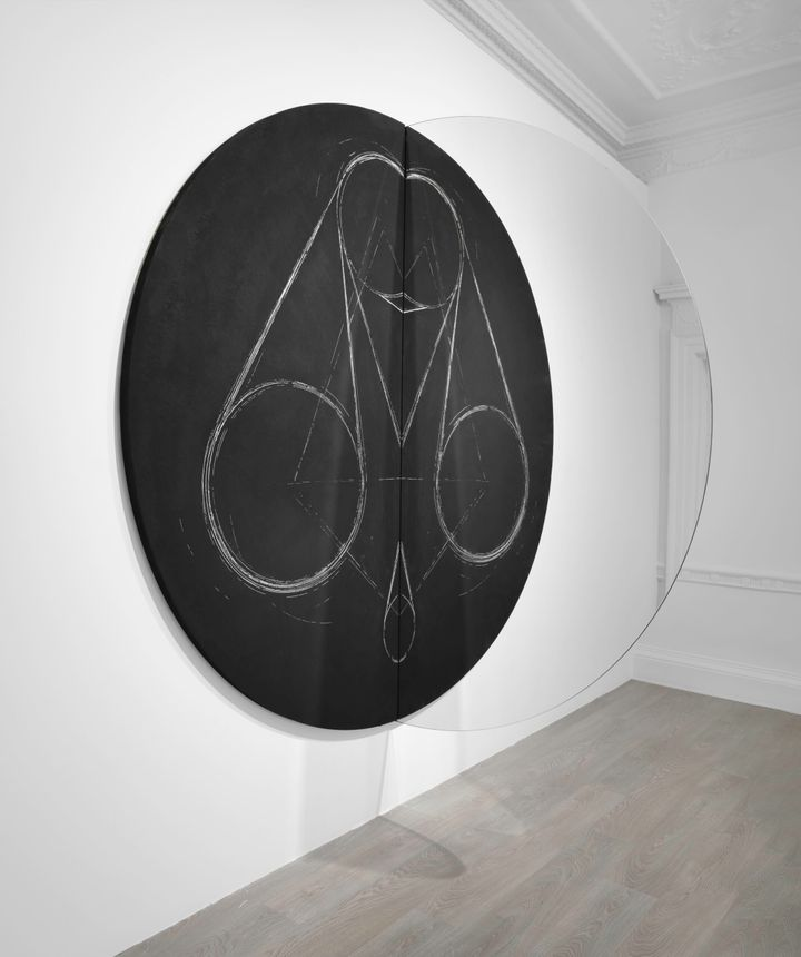 A large circular black canvas with chalk drawn circular motifs by Marco Tirelli is divided in half by a mirror. The sculptural piece hangs in the gallery space.