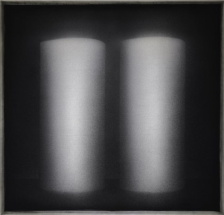 Two cylindrical forms appear from a black background.