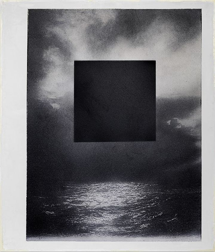 A grainy, black and white image of the ocean beneath a cloudy sky is overlaid with a large black square, in a mixed media work by Marco Tirelli.