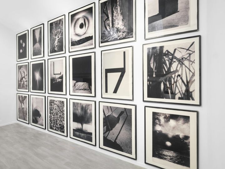 Three rows of black and white photographs, with 6 images in each row, hang along a wall in a white gallery space. Each image shows imagery including a tornado, shadows on the ground, and ribbons in the air.