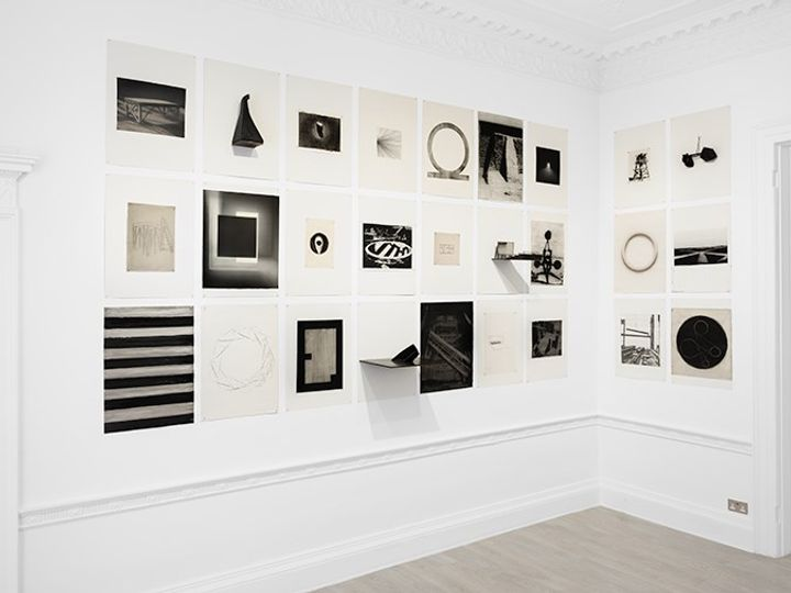 Two walls in a white gallery space are filled with black and white geometric imagery in varying sizes by Marco Tirelli.