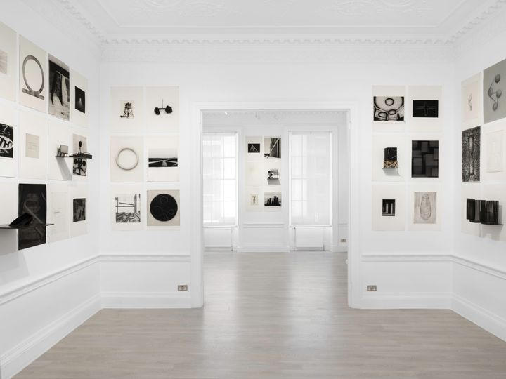 Black and white geometric imagery in varying sizes fill the walls of a white gallery space.