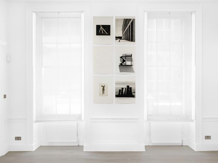 Six black and white geometric works by Marco Tirelli line the wall that sits between two windows in a white gallery space. Three rows of two images on each feature architectural imagery.