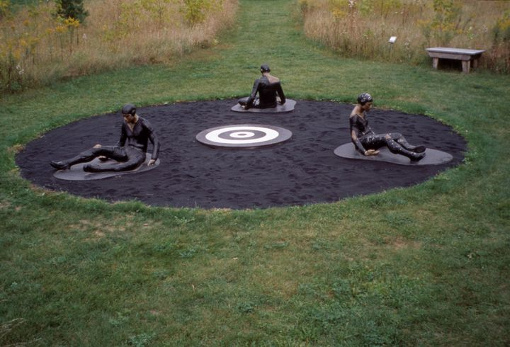 Three sculptures of pilots are seated in a circle in a work by Michael Richards. Each pilot appears to be drenched in tar and stuck to the ground.