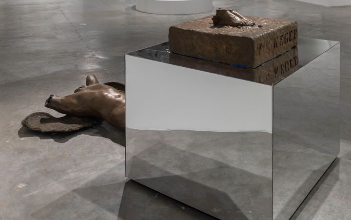 Atop a mirrored cube in the exhibition space is a small bronze plinth that reads 'Tuskegee', upon which a pair of feat are placed. The bust of a fallen figure rests on the floor beside the cube.