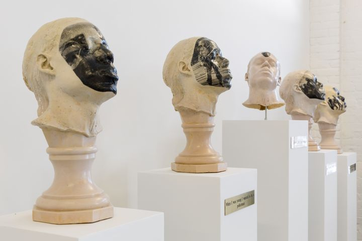 A series of five plaster heads are placed on a plinth each. Each face features black and white newspaper imagery of police in riot gear, except for the central head which features a black and white portrait of activist Rodney King.