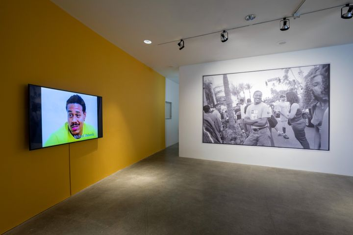 A room in the exhibition space features one yellow wall with a video placed on it, from which a male figure is captured in the midst of speaking. To the right, a white wall features a black and white archival image of the artist Michael Richards.