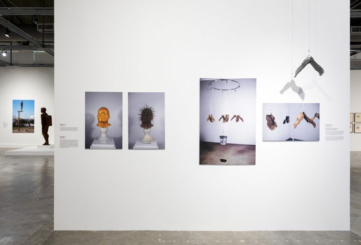 Archival imagery of sculptures by Michael Richards feature on a white wall of the exhibition space, including images of heads as well as hanging wings.